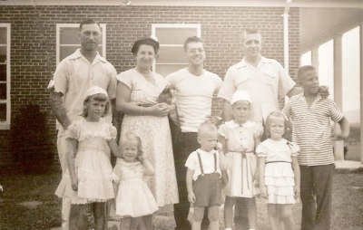 A group of parishioners gather for a picture near the side of the ChurchThe photo is stamped August 56